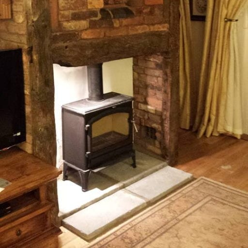 Log-burner-fitted-in-brick-and-wooden-feature-fireplace